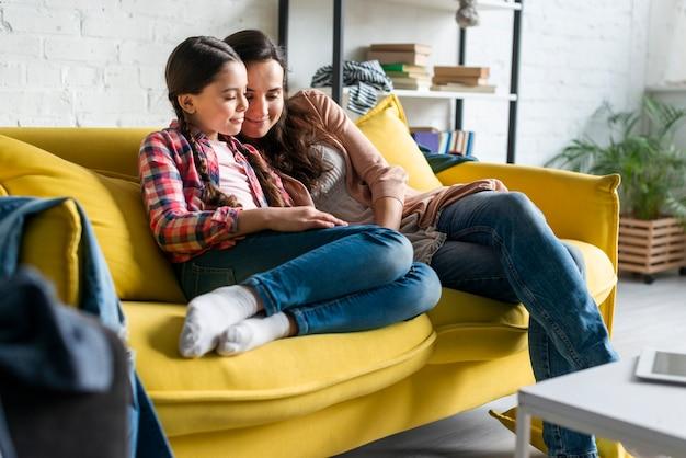 Moeder en dochterzitting op gele bank Gratis Foto
