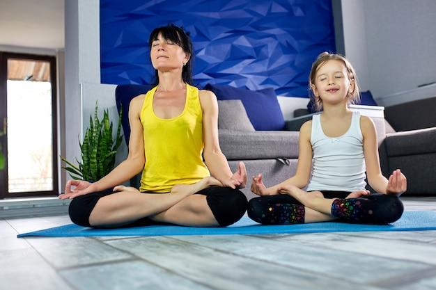 Moeder en haar dochter die yoga samen thuis doen. Premium Foto