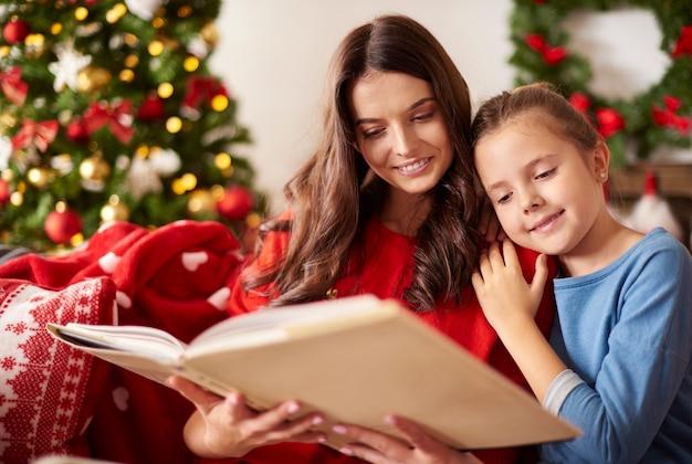 Moeder en haar dochter lezen een boek met kerstmis Gratis Foto