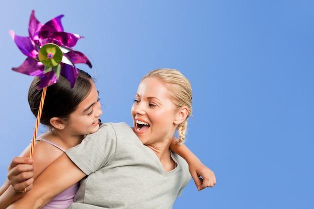 Moeder en haar dochter met een windmolen Premium Foto