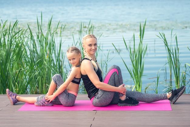 Moeder en haar dochtertje zitten naast elkaar op de roze rolmat bij het meer op een pier Premium Foto