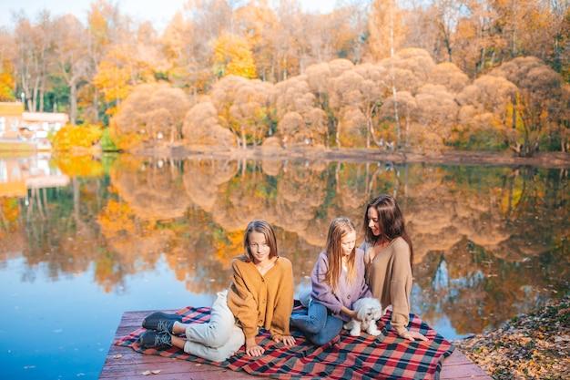 Moeder en haar kleine dochters in de herfst op picknick op het meer Premium Foto