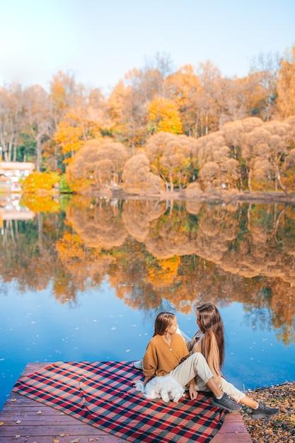 Moeder en haar schattige dochters genieten van herfstdag op het meer Premium Foto