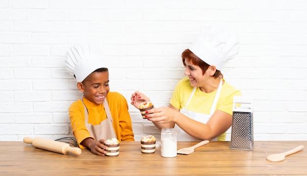 Moeder en haar zoon kleedden zich als chef in een keuken Premium Foto