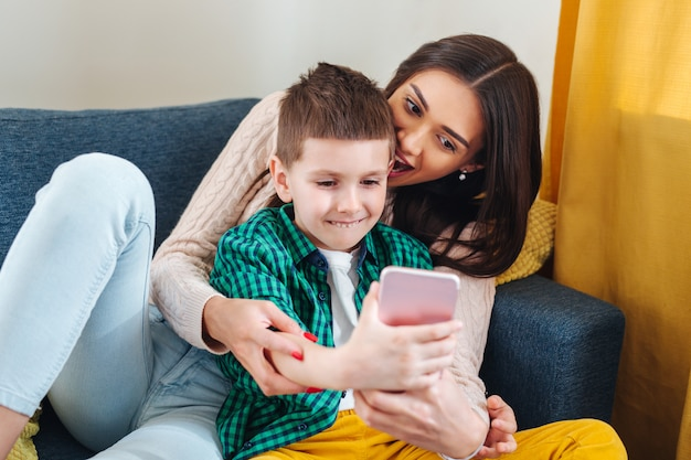 Moeder en haar zoontje maken selfie thuis Premium Foto
