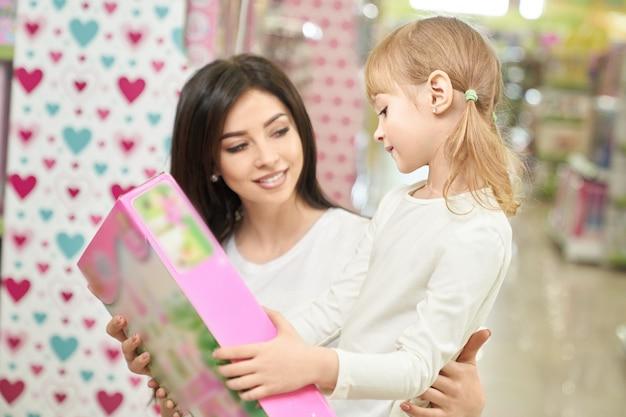 Moeder en kind die en stuk speelgoed in opslag kijken kiezen. Gratis Foto