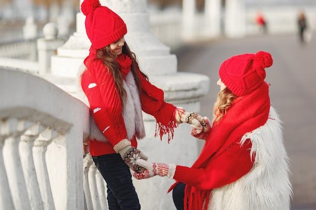 Moeder en kind in gebreide wintermutsen op familiekerstvakantie. handgemaakte wollen muts en sjaal voor mama en kind. Gratis Foto