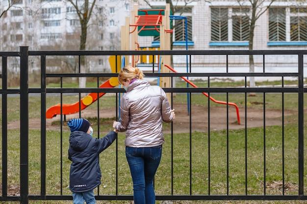 Moeder en kind in medische maskers kijken elkaar aan Premium Foto