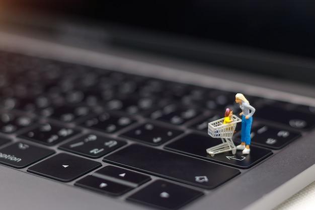 Moeder en kind met het winkelen kaart die zich op laptop toetsenbord bevindt. Premium Foto