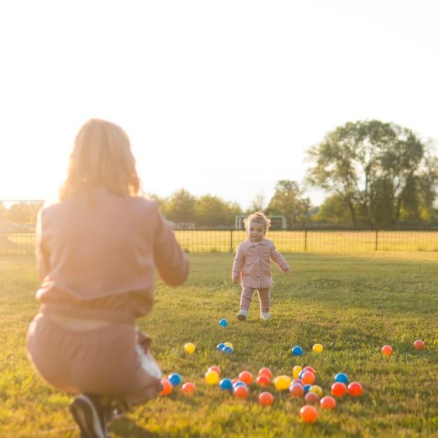 Moeder en kind spelen met plastic ballen in het park Gratis Foto