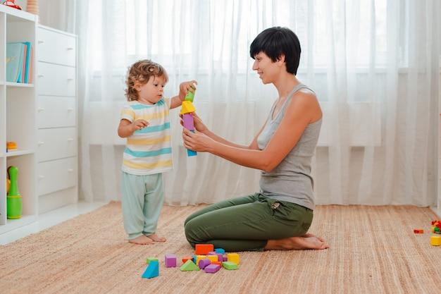 Moeder en kind spelen op de vloer in de kinderkamer. moeder en een kleine jongen bouwen een toren van gekleurde blokken. Premium Foto