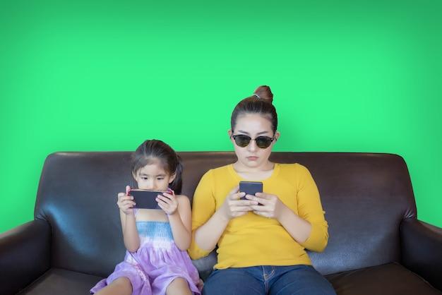 Moeder en kind verslavend mobiele telefoon spelen op groen scherm Premium Foto