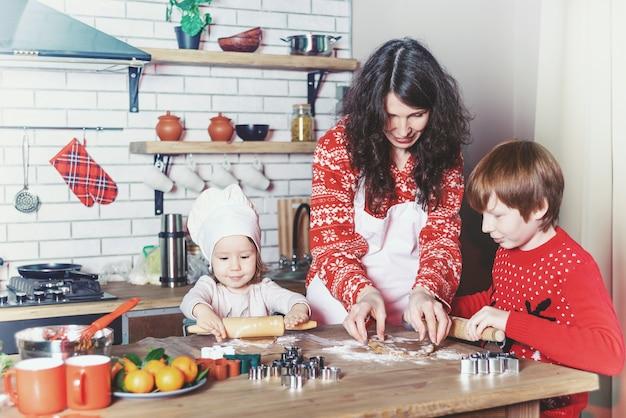 Moeder en kinderen bakken koekjes in de keuken en versieren koekjes op kerstavond Premium Foto