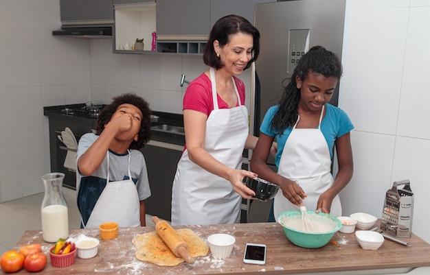 Moeder en kinderen die lunch samen in de keuken voorbereiden Premium Foto