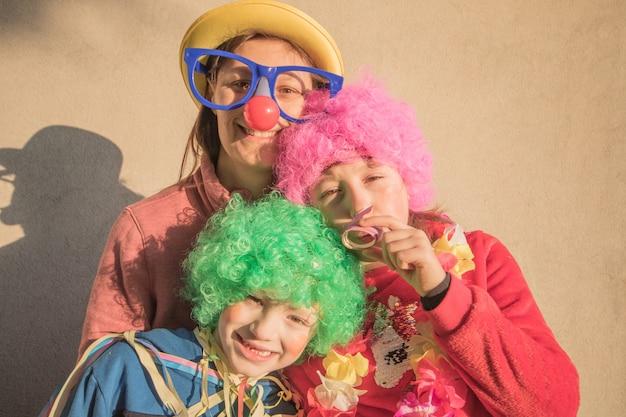 Moeder en kinderen in carnaval-masker samen glimlachen openlucht Premium Foto