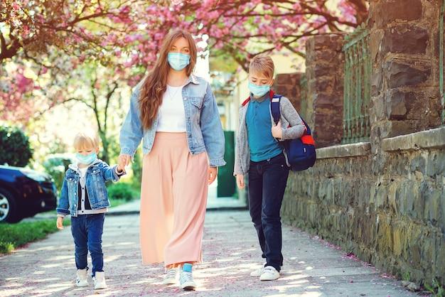 Moeder en leerling van de basisschool gaan hand in hand. triest gezin naar huis tijdens quarantaine. Premium Foto