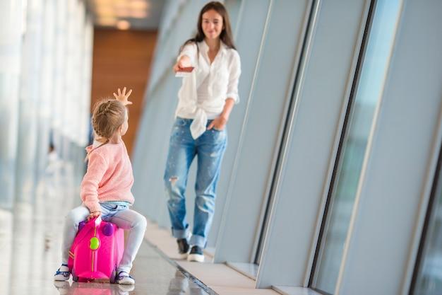 Moeder en meisje die met instapkaart bij luchthaventerminal de vlucht wachten Premium Foto
