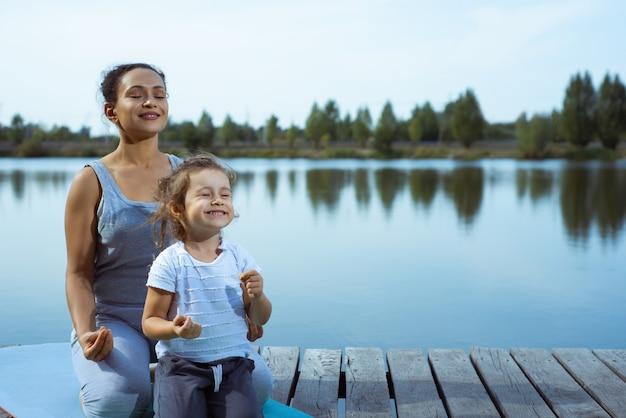 Moeder en meisje doen yoga Premium Foto
