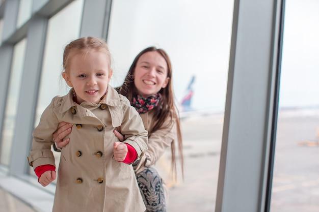 Moeder en meisje in luchthaven wachten op instappen Premium Foto