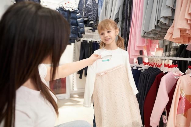 Moeder en meisje op zoek, roze jurk kiezen. Gratis Foto