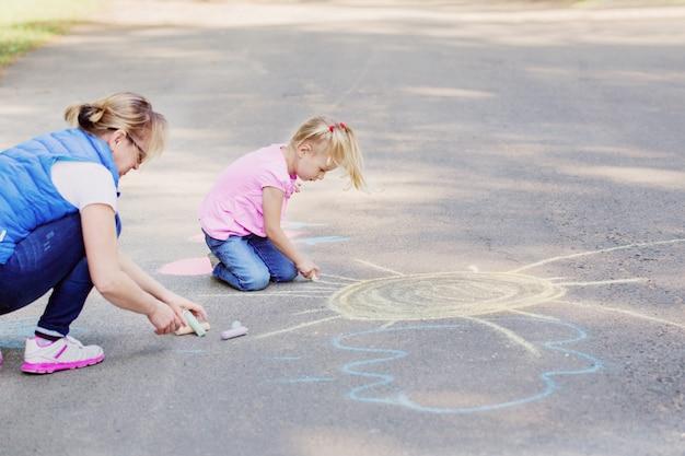 Moeder en meisje trekt met krijt op de stoep Premium Foto