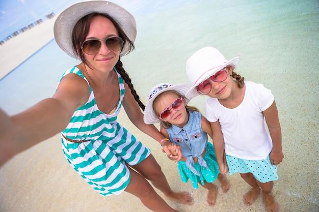 Moeder en meisjes die selfie bij tropisch strand nemen Premium Foto