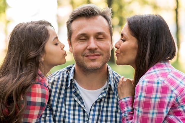 Moeder en schattige dochter zoenen vader in park Gratis Foto