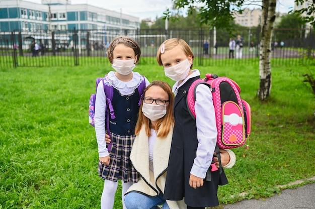 Moeder en schattige dochters met gezichtsmasker voor veiligheidsbescherming. schoolmeisjes klaar voor school. Premium Foto