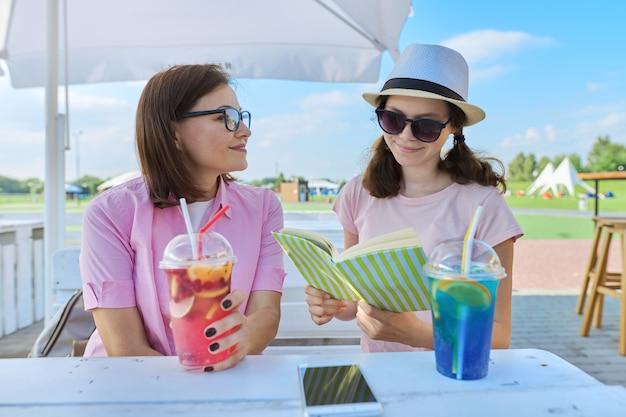 Moeder en tienerdochter samen in zomerterras café met frisdranken boek kladblok lezen Premium Foto