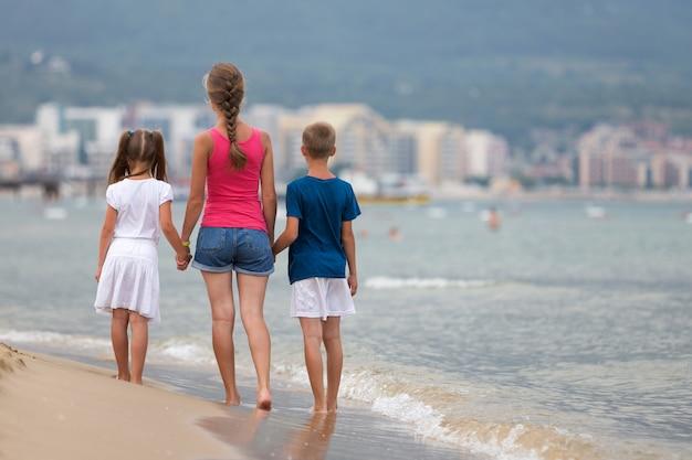 Moeder en twee kinderen zoon en dochter lopen samen op zandstrand in zeewater in de zomer met blote voeten in warme oceaan golven. Premium Foto
