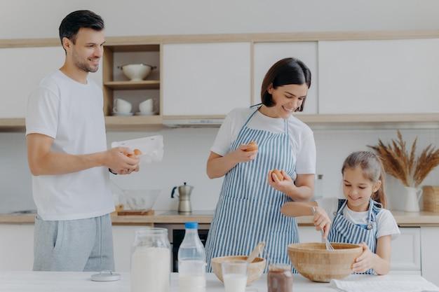 Moeder en vader geven eieren aan dochter die deeg bereidt, bezig is samen te koken tijdens het weekend, gelukkige buien heeft, eten klaarmaakt. drie familieleden thuis. ouderschap en samenhorigheid concept Premium Foto