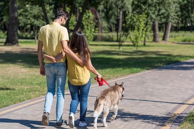 Moeder en vader in het park die de hond uitlaten   Gratis Foto