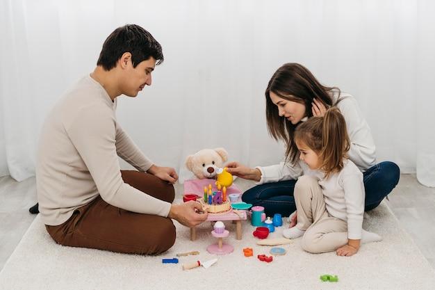 Moeder en vader spelen met dochter thuis Gratis Foto