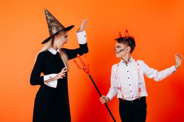 Moeder en zon in duivelse make-up maken elkaar bang. halloween Premium Foto