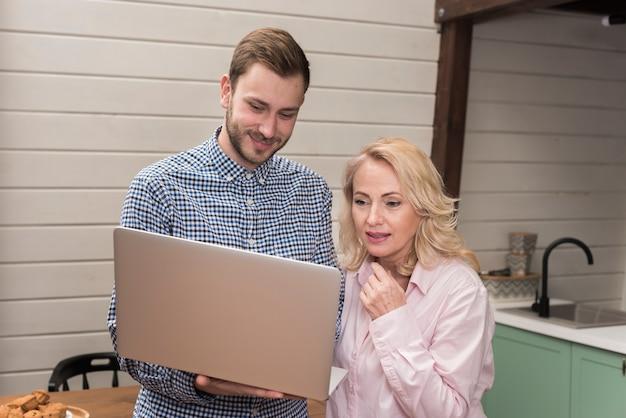 Moeder en zoon die laptop in de keuken bekijken Gratis Foto