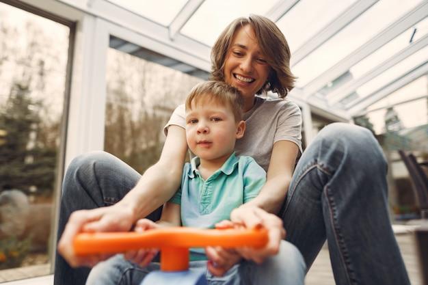 Moeder en zoon gaan rond in het appartement op een speelgoedauto Gratis Foto