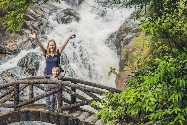 Moeder en zoon in het oppervlak van de prachtige trapsgewijze datanla waterval in het bergstadje dalat, vietnam Premium Foto