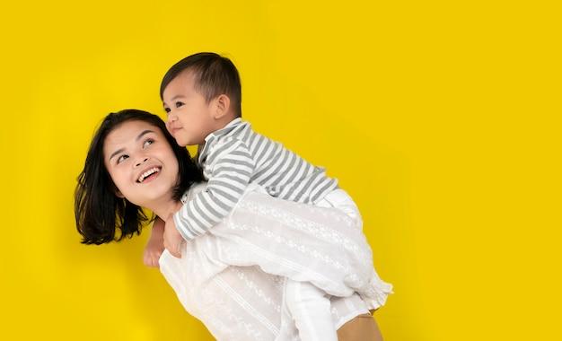 Moeder en zoon knuffelen, lachen en spelen samen op gele achtergrond. gelukkige familie momenten. Premium Foto