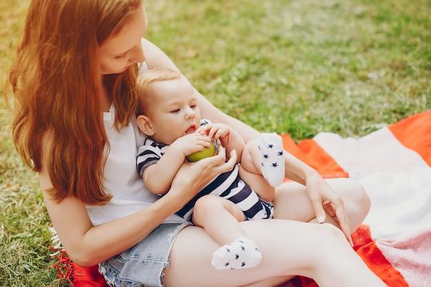 Moeder en zoon ontspannen in het park. Gratis Foto