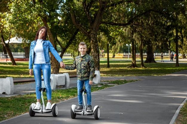 Moeder en zoon rijden op een hoverboard in het park Premium Foto