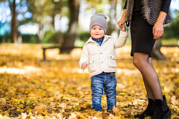 Moeder en zoon wandelen in een herfstpark Gratis Foto