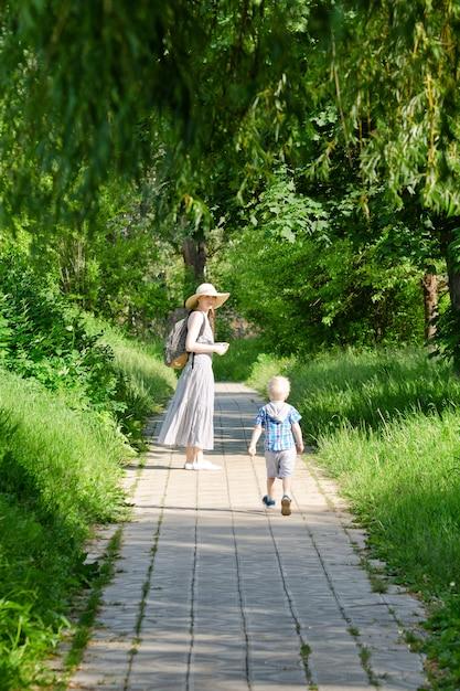 Moeder en zoon wandelen langs de weg in het park. achteraanzicht. verticaal frame Premium Foto