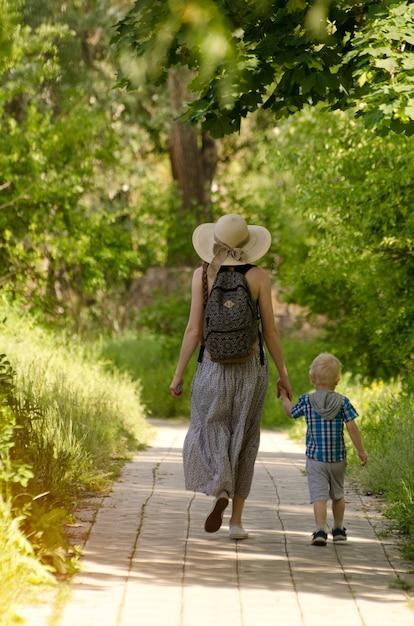 Moeder en zoon wandelen langs de weg in het park. Premium Foto