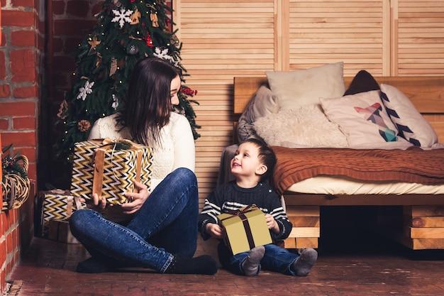 Moeder en zoon zitten op de grond en houden kerstcadeautjes vast. Premium Foto
