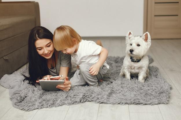Moeder en zoontje plezier thuis met hond Gratis Foto