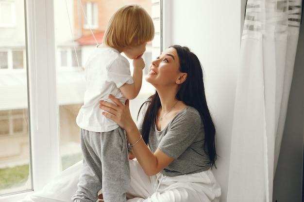 Moeder en zoontje zittend op een vensterbank Gratis Foto