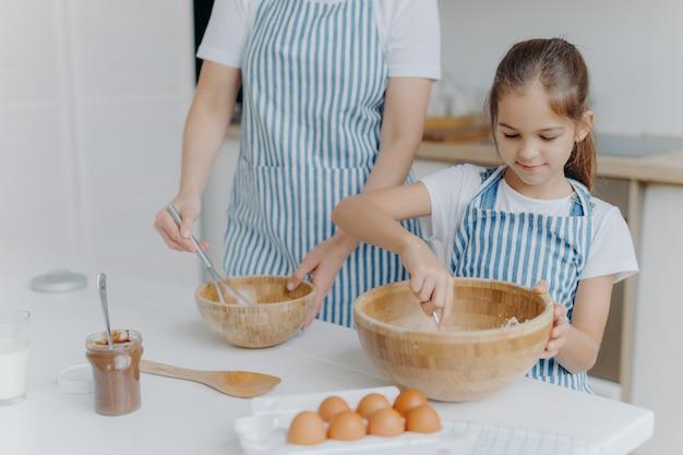 Moeder geeft culinaire les aan klein kind, sta naast elkaar, meng ingrediënt in grote houten kommen Premium Foto