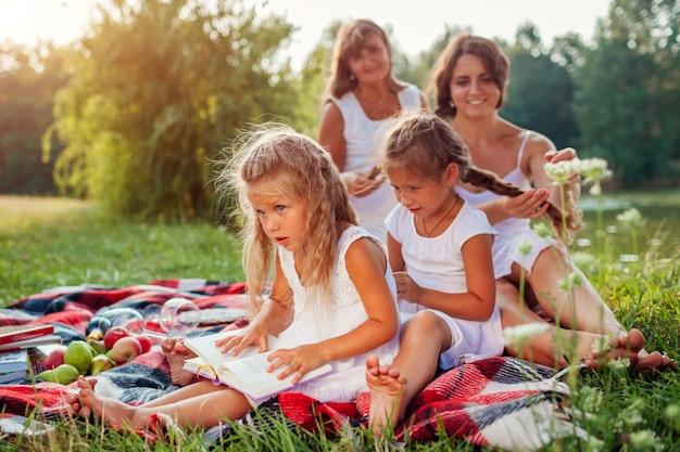 Moeder, grootmoeder en kinderen vlechten elkaar, familie plezier tijdens picknick in het park, Premium Foto