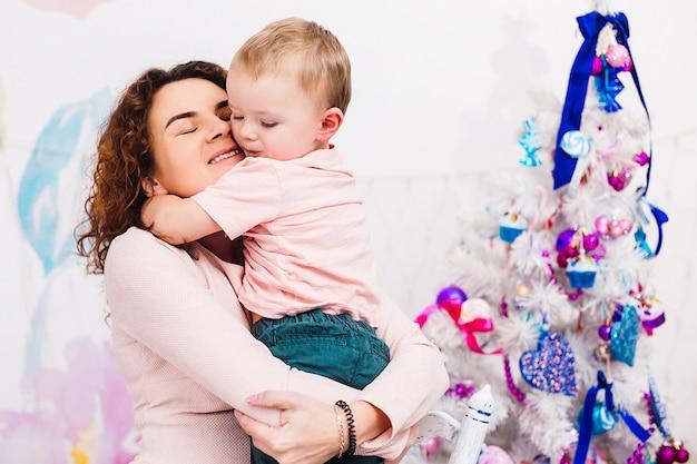 Moeder heeft plezier met haar zoon, zittend in de kamer, gekleed voor kerstmis en nieuwjaar Gratis Foto