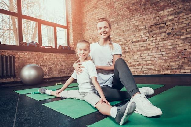 Moeder helpt dochter op touw in de sportschool te zitten. Premium Foto